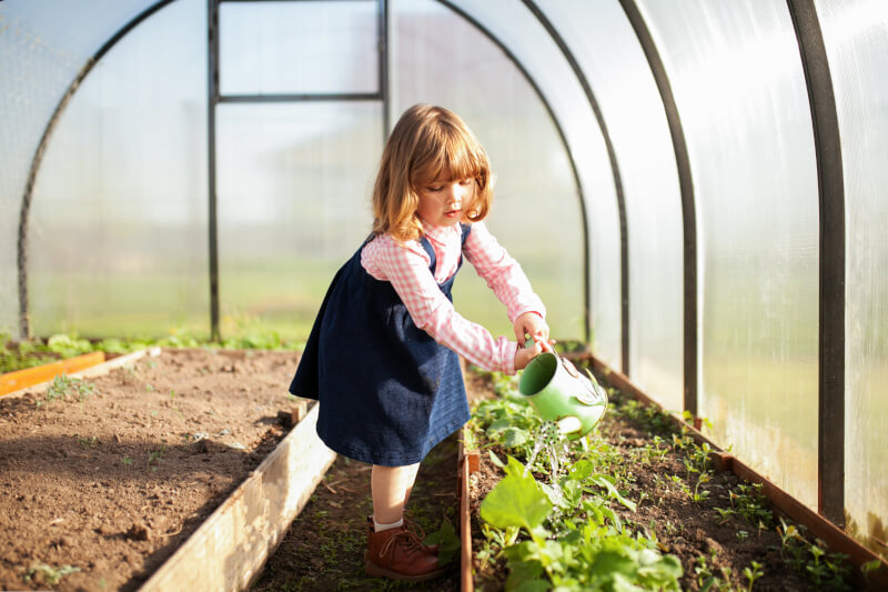 home greenhouse with girl watering plants